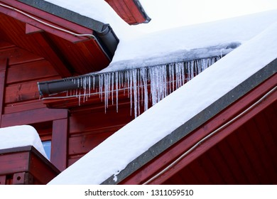 Sharp icicles and melted snow hanging from eaves of roof