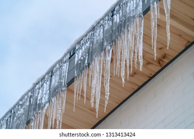 Sharp icicles on the eaves of a roof in Utah