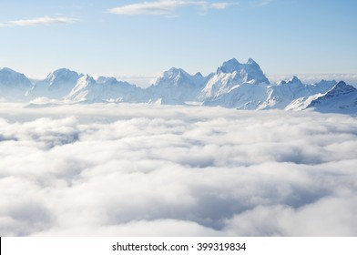 Sharp mountain peaks sticking out of clouds