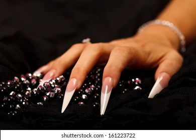 A sharp nailed woman's hand with pearls isolated on black