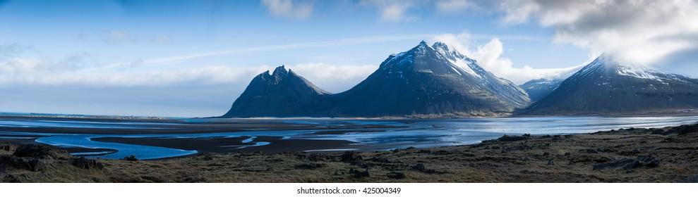 Sharp peaks mountain ranges on coast in Iceland