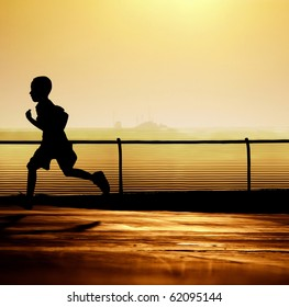 Sharp silhouette of a boy running with a beautiful sunset in the background.