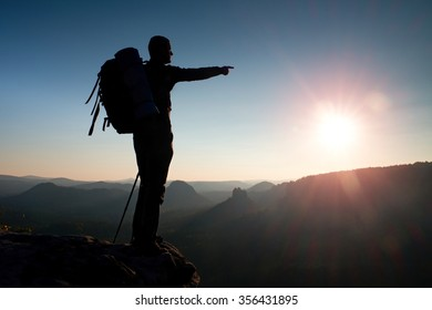 Sharp silhouette of a tall man on the top of the mountain with sun in the frame