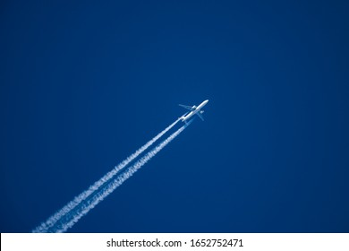 Sharp, telephoto close-up image of jet plane, aircraft with contrails cruising at 35,000 feet Tokyo to NY ground speed 480 knots