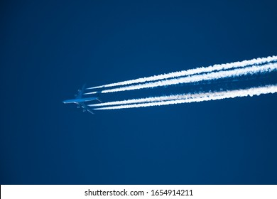 Sharp, telephoto close-up image of jet plane, aircraft with contrails cruising at 35,000 feet Seoul to NY ground speed 473 knots