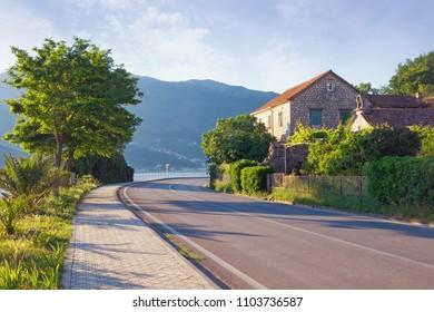 Sharp turn of road. View of Adriatic Highway (Jadranska magistrala) running along the coast of Bay of Kotor . Montenegro, Donja Lastva village