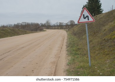 Sharp turn with warning sign on a gravel road