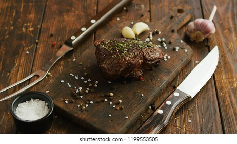 Sharp utensils and aromatic spices lying on timber tabletop near wooden cutting board with piece of tasty fried meat