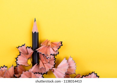 Sharpened black pencil over yellow background