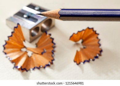 Sharpened pencil with a metal sharpener in the background