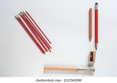 sharpened pencils and pencil sharpener on a white sheet