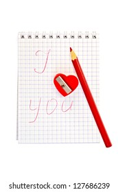 Sharpener in the shape of a red heart with a pencil and a notebook labeled isolated on white background