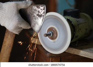 Sharpening an ax on a sharpener close-up