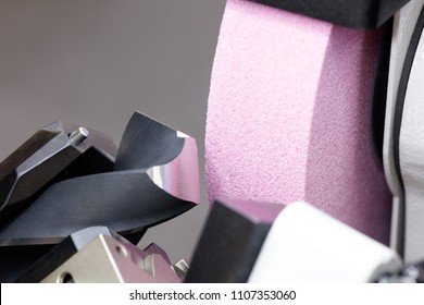 Sharpening drill bits on a grinding machine  industrial engineering concept.