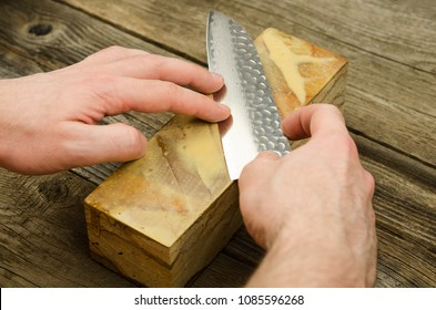 Sharpening Japanese knife with whetstone. Santoku knife sharpening. Honing chef knife. Close up of hands sharpening Japanese chef knife.