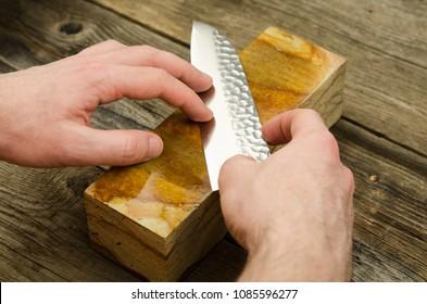 Sharpening Japanese knife with whetstone. Santoku knife sharpening. Honing chef knife. Close up of hands sharpening Japanese chef knife.