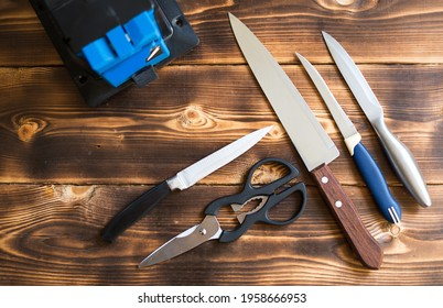 Sharpening a knife on an electric sharpener at home. Layout of knives and scissors with a sharpening machine on a wooden table. Top view, flat lay.