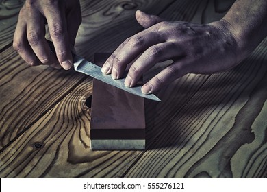 Sharpening the knife with a whetstone on a wooden background.