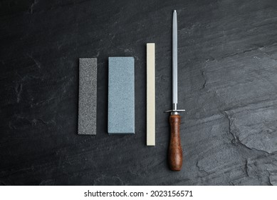 Sharpening stones and honing steel on black table, flat lay