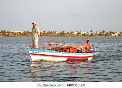 Sharqi Island, Kerkennah archipelago / Tunisia - March/28/2019 : Two fishermen on board of a traditional colored fishing boat leaving to sea, Tunisia