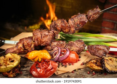 Shashlik or shish kebab prepared on barbecue grill over hot charcoal with grilled vegetables. Grilled pieces of pork meat on metal skewers.