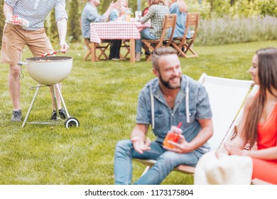 Shashliks being put on a grill by a man during a BBQ party. Blurred foreground with a woman and a man sitting on deckchairs and talking. Other people by a table in the background.