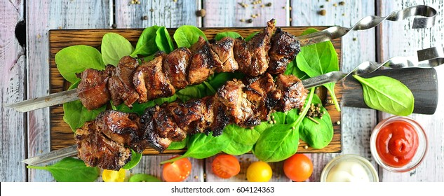 Shashly pork on skewers on a dark wooden board with tomatoes, spinach and sauces, wooden light background with copy space