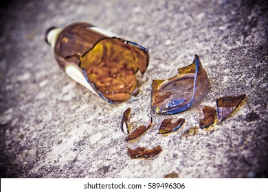 Shattered beer bottle resting on the ground: alcoholism concept - toned image