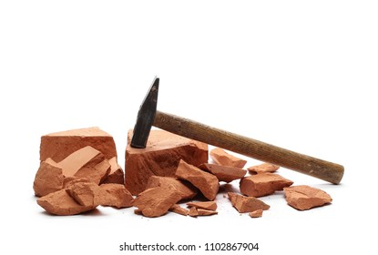 Shattered brick pieces and hammer isolated on white background