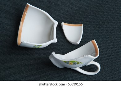 Shattered coffee cup on a black cloth