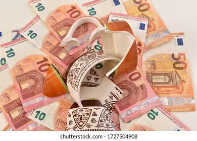 Shattered cup on top of euro bills symbolizing economic fallout due to coronavirus pandemic crisis.