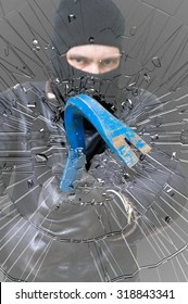 Shattered glass. Burglar or thief masked with balaclava is breaking glass with crowbar.