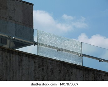 shattered glass railing balustrade panel above stone panel. blue sky. white clouds. broken laminated tempered safety glass. construction and building industry concept. stainless steel glass brackets.