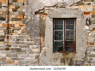 A shattered window on an aged brick wall. This is a wall from a house of traditional chinese village.