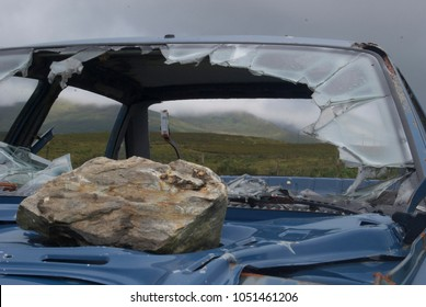 Shattered windshield of a blue car frame in a hilly Irish landscape