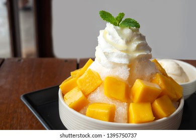 Shaved ice dessert with mango sliced.  Served with vanilla ice cream and whipped cream. Sweet dessert in Korean style. Local name, Bingsu.