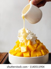 Shaved ice dessert. Woman hand pouring sweetened condensed milk on whipped cream. Served with mango sliced and vanilla ice cream. Sweet dessert in Korean style. Local name, Bingsu.
