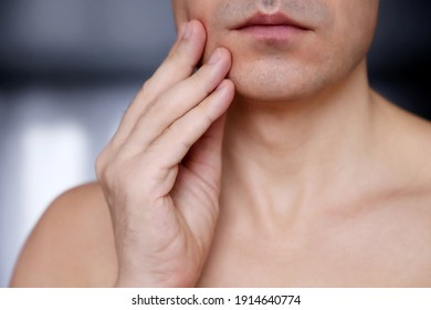 Shaved male face close up. Man touching his chin, beauty and skin care concept