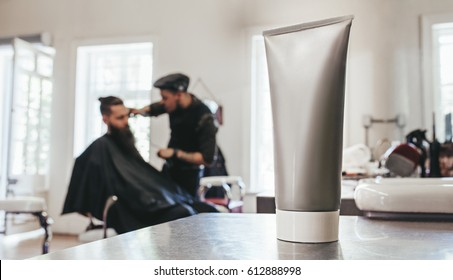 Shaving cream tube on counter with barber serving client in background.