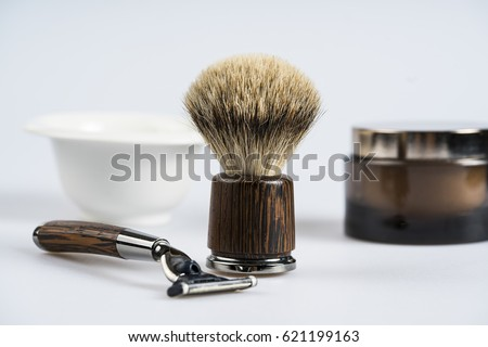Shaving tools are displayed with a bottle of shaving cream and a cup containing of soap. / Shaving tools.