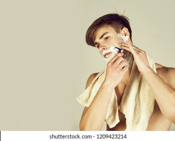shaving. Young man or handsome macho shaving bearded face chin with safety razor and white cream or foam with bathing towel on neck on grey background. skincare, hygiene, grooming, copy space