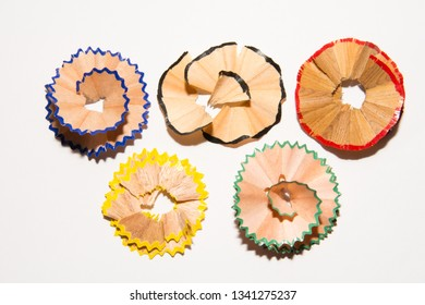 Shavings from a pencil on a white sheet of paper. On white background. The patterns of the chips. The image of the Olympic rings of chips. Hone your skills.