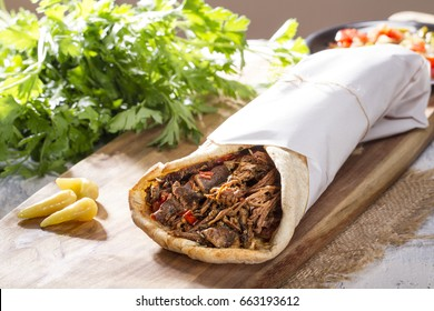 Shawarma ; Grilled Lamb Kebab Doner Wrap with yogurt, pickle, onion, aubergine and tomato on rustic white painted rustic wood table.