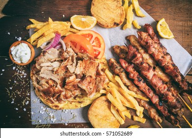 Shawarma, gyros dish and greek souvlaki on a wooden background, top view