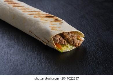 Shawarma kebab with beef on black textured stone