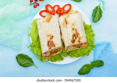 Shawarma - Middle Eastern dish made from lavash (pita), stuffed with chicken, mushrooms, fresh vegetable salad, sauce. Serving on lettuce leaves on a light background. The top view.