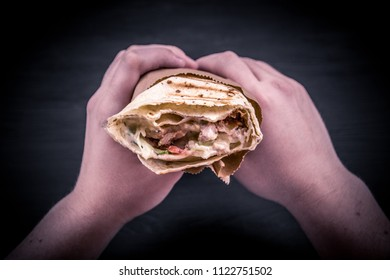 shawarma on a black background hold in hands