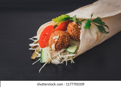 Shawarma sandwich falafel - fresh roll of thin lavash (pita bread) filled with grilled meat, mushrooms, cheese, cabbage, carrots, sauce, green. Traditional Eastern snack. On a wooden background.