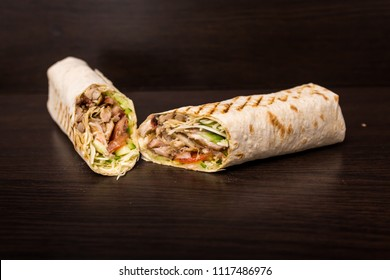 Shawarma sandwich - fresh roll of thin lavash (pita bread) filled with grilled meat, mushrooms, cheese, cabbage, carrots, sauce, green. Traditional Eastern snack. On a wooden background.