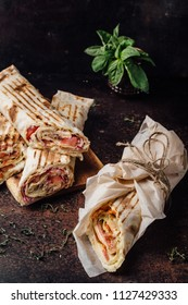 Shawarma Sandwich - a fresh roll of thin lavash, filled with grilled meat, mushrooms, cheese and herbs. Oriental snack. On a metal background.